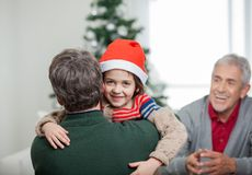 Happy Boy Embracing Father During Christmas. Portrait of happy boy embracing father with grandfather looking at them during Christmas at home Royalty Free Stock Image