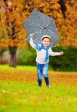 Happy boy enjoying an autumn rain in park Stock Photography