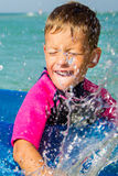Happy boy enjoying swimming in sea with rubber Stock Photography