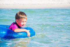 Happy boy enjoying swimming in sea with rubber Stock Images