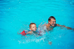 Happy boy enjoying with swimming and splashing with his father. Royalty Free Stock Photos