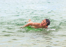 Happy boy enjoys crawling in the ocean Royalty Free Stock Photography