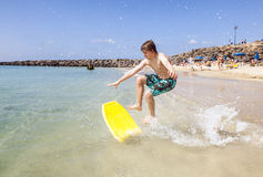 Happy boy enjoys surfing. In the waves at the beach stock photos