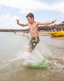 Happy boy enjoys surfing. In the waves at the beach royalty free stock photos