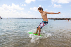 Happy boy enjoys surfing in the waves. At the beach royalty free stock image