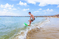 Happy boy enjoys surfing in the waves. At the beach royalty free stock images