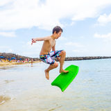 Happy boy enjoys surfing. In the waves at the beach royalty free stock photo