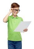 Happy boy in eyeglasses holding school test result Stock Photography