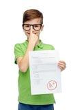 Happy boy in eyeglasses holding school test result Royalty Free Stock Photos