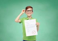 Happy boy in eyeglasses holding school test result Royalty Free Stock Images