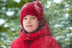 Happy boy with falling snow in the forest Stock Image