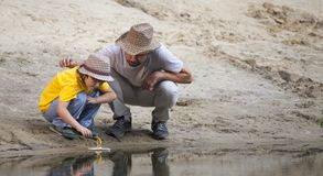 Happy boy and father go fishing on the river, children with a fi Royalty Free Stock Photos