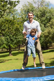 Happy boy and father jumping high on trampoline in park Royalty Free Stock Images