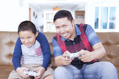 Happy boy and father playing video games. Portrait of happy little boy and his father playing video games together at home stock photo