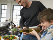 Happy Boy And Father Preparing Salad In Kitchen Stock Photos