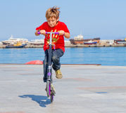 Happy boy faving fun on scooter on natural background Royalty Free Stock Images