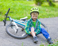 Happy boy fell from the bike in a park.  Royalty Free Stock Photo