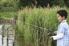Happy Boy Fishing In Lake Stock Images