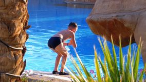 Happy boy in flippers jumping into the blue water pool. Slow motion. Happy boy in flippers jumping into the pool with blue water. Slow motion in 180 fps. The stock video