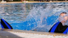 Happy boy with flippers swims in a pool with blue water. Slow motion. In 180 fps. The child fun floundering in the clear, transparent water of the pool by the stock footage