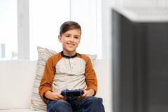 Happy boy with gamepad playing video game at home royalty free stock image