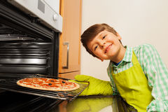 Happy boy getting delicious pizza from the oven Stock Photography