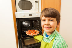 Happy boy getting out of the oven baked pizza Stock Image