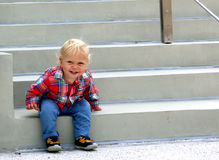 Happy baby boy is getting up from the stairs Stock Image