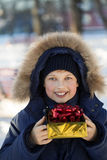 Happy boy with gift box. Outdoors Royalty Free Stock Images
