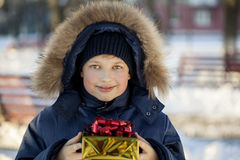 Happy boy with gift box. Outdoors Royalty Free Stock Photos