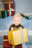 Happy boy with gift in hands. Sitting on white stairs Stock Photo
