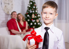 Happy boy with gift from his parents and Christmas tree Stock Photography