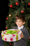 Happy boy with gift in their hands. Near  Christmas tree Stock Image