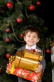 Happy boy with gift in their hands. Near  Christmas tree Royalty Free Stock Image