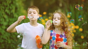 Happy boy and girl blowing soap bubbles in summer park. stock footage