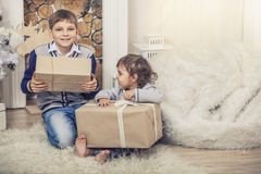 Happy boy and girl with boxes of gifts in the Christmas interior Royalty Free Stock Image