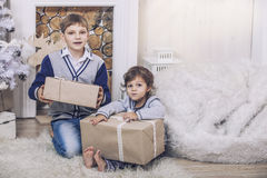 Happy boy and girl with boxes of gifts in the Christmas interior Royalty Free Stock Images
