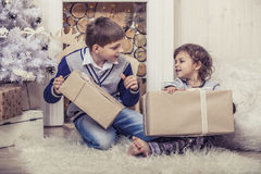 Happy boy and girl with boxes of gifts in the Christmas interior Royalty Free Stock Photography