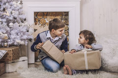 Happy boy and girl with boxes of gifts in the Christmas interior Stock Photo