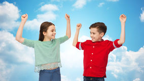 Happy boy and girl celebrating victory over sky Stock Images