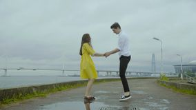 Happy boy and girl dance emotionally some joyful jive on a pier on a sea coast