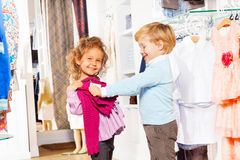 Happy boy with girl fitting sweater in store Stock Images