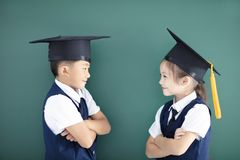 Boy and girl in graduation cap in classroom. Happy boy and girl in graduation cap in classroom stock photography