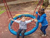 Happy boy and girl have a swing on the Playground. stock photos