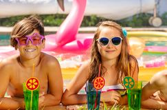 Happy boy and girl having fun during pool party. Happy teenage boy and girl in sunglasses having fun during pool party in summer stock photos