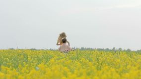 Happy boy and girl having fun, running around the meadow with yellow flowers. Brother and sister playing in the canola field. Happy boy and girl having fun stock video footage