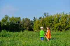 Happy boy and girl holding hands playing on a meadow in sunny day. Happy boy and girl holding hands playing on a meadow in a sunny day. Children run through the Royalty Free Stock Photography
