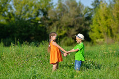 Happy boy and girl holding hands playing on a meadow in  sunny day. Happy boy and girl holding hands playing on a meadow in a sunny day. Children run through the Stock Photos