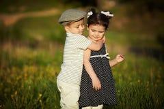 Happy boy and girl hug. In summer field Stock Photo