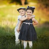 Happy boy and girl hug. In summer field Royalty Free Stock Images